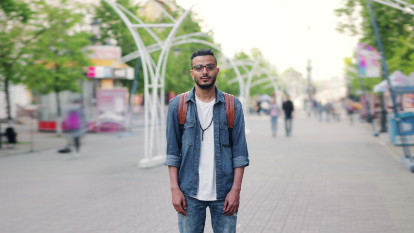 Time lapse portrait of Middle Eastern man with backpack standing in the street alone looking at camera when people are passing by. Youth and travelling concept.