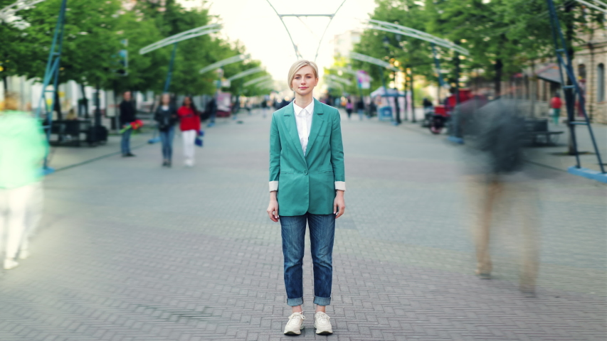 Time lapse portrait of attractive blonde standing outdoors in the street alone wearing stylish clothes and looking at camera. Urban lifestyle and young people concept.