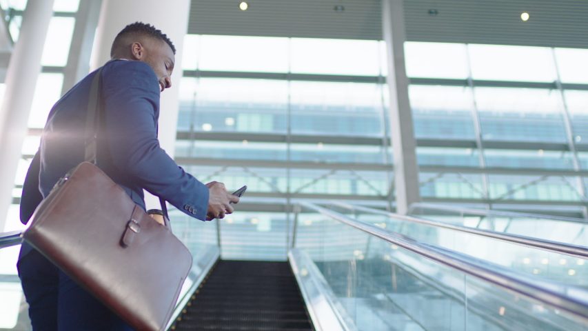 Young african american businessman using smartphone on escalator texting checking email messages online successful male executive arriving at work in corporate office building 4k | Shutterstock HD Video #1032464945