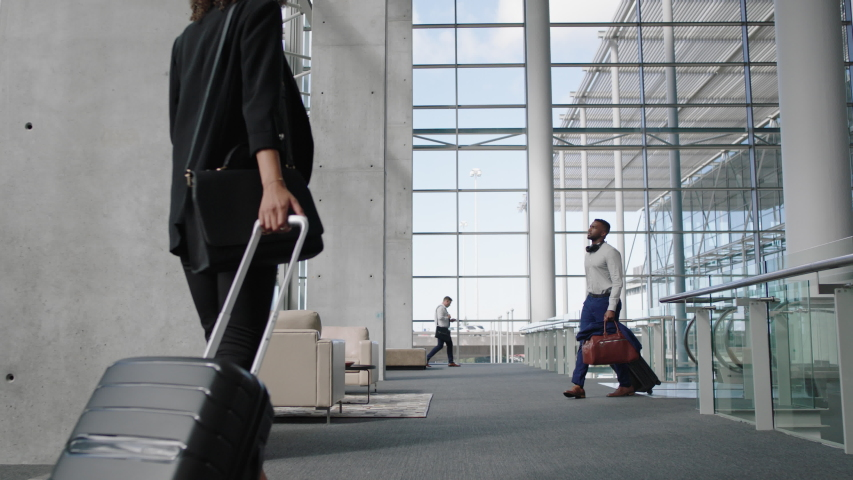 Diverse people at busy airport pulling trolley bags arriving and departing terminal tourists travelling international walking in lobby with luggage on the move 4k footage