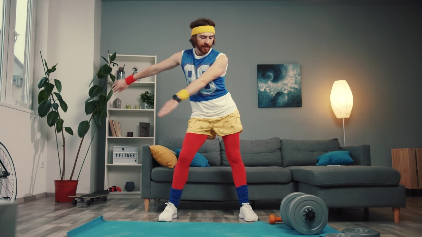 Funny stupid-looking reto fitness man dancing enjoying music and warming up on workout in the living room. | Shutterstock HD Video #1032466298