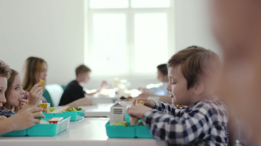 Cute little pupils having a tasty lunch between lessons at a a school. Portrait of a hungry sweet boy eating his snacks with taste sitting with classmates.