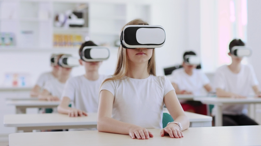 Cheerful young students wearing VR headsets listening to commands giving thumbs up to the teacher during a class. | Shutterstock HD Video #1032466826