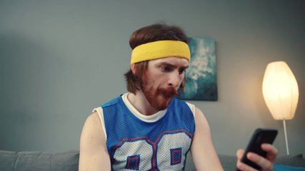Portrait of sexy fit man in retro outfit training hard with light dumbbells playing on camera recording a sports vlog indoors.