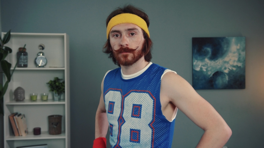 Portrait of amazed young bearded man hipster in retro sports outfit looking with a surprised expression standing in his living room at home.   Shutterstock HD Video #1032467519