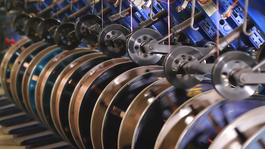 Steel wire coils at a tire factory. Rotating and reeling metal threads bobbins long line at modern tire production plant. Bronze wire is fed for the manufacture of the side rings of automotive wheels. | Shutterstock HD Video #1032467630