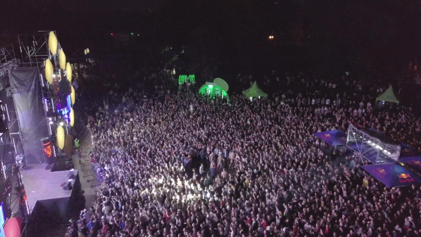 KYIV-25 MAY,2019:Aerial drone footage of summer music festival crowd partying to popular edm dj set on dancefloor.EDM music festival event shot from above view flying video camera at night concert gig