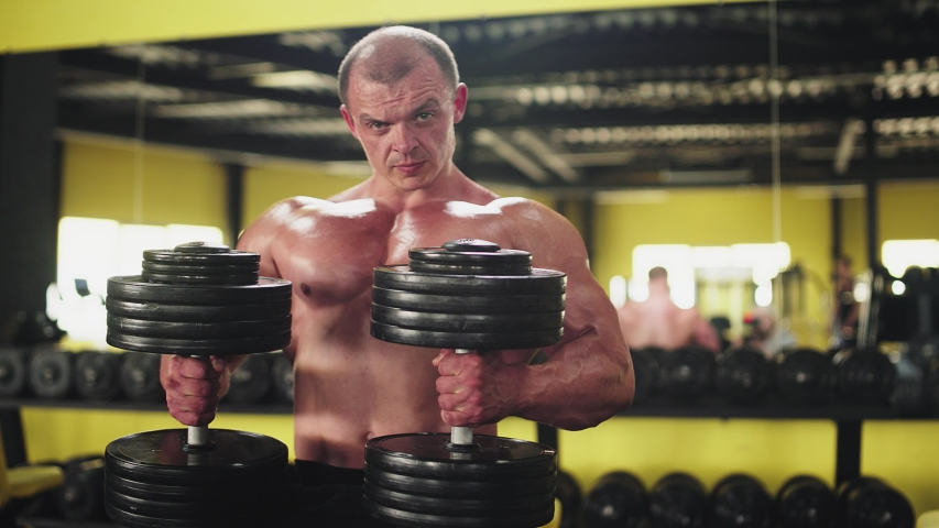 Lifting dumbbells for bigger biceps close up. Close up handsome man with big biceps lifting weights | Shutterstock HD Video #1032475811