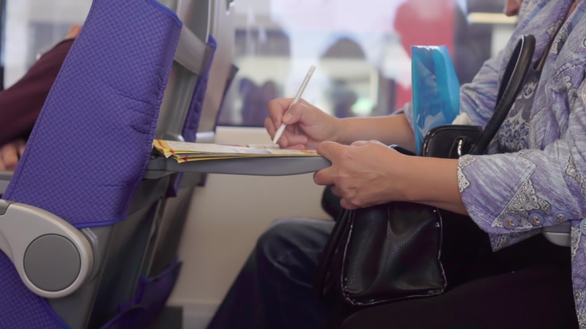 woman solving crossword puzzle while sitting in the train #1032492464