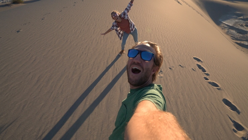 Couple traveling takes selfie picture on sand dunes at sunset. Young couple taking selfies in wester USA. People travel concept.