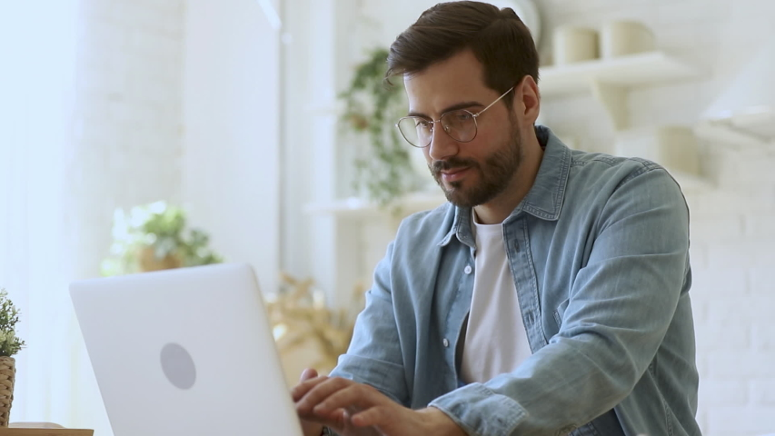 Young man freelancer student using laptop studying online working from home in internet, smiling focused millennial guy typing on computer surfing web looking at screen enjoying distant job #1032517127