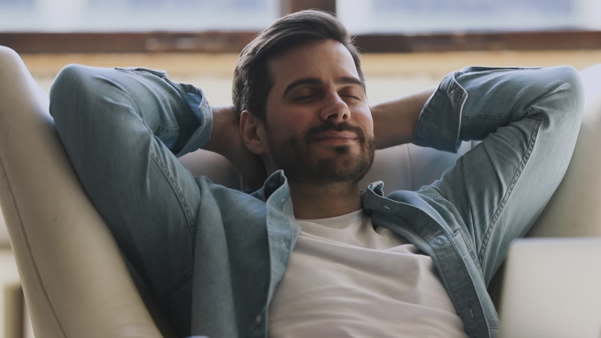 Calm happy healthy young man resting holding hand behind hand eyes closed lean on comfortable armchair, relaxed serene guy breathing fresh air lounge on chair enjoy stress free peaceful nap at home