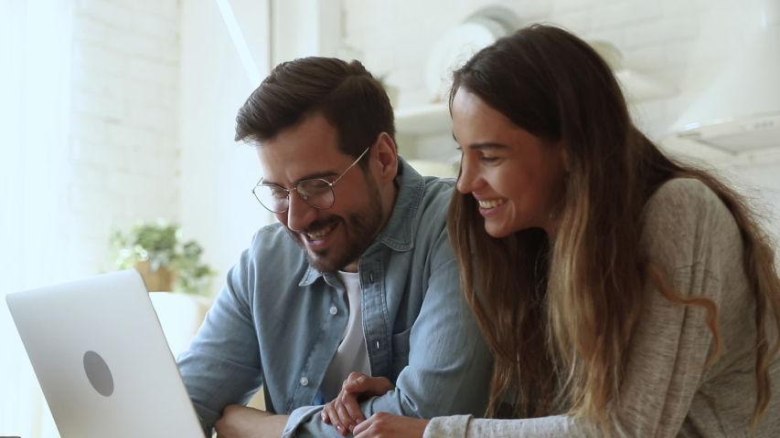 Happy young family couple talking bonding laughing using laptop computer looking at screen doing internet shopping together at home, smiling man and woman buying goods online on website in kitchen Royalty-Free Stock Footage #1032517139