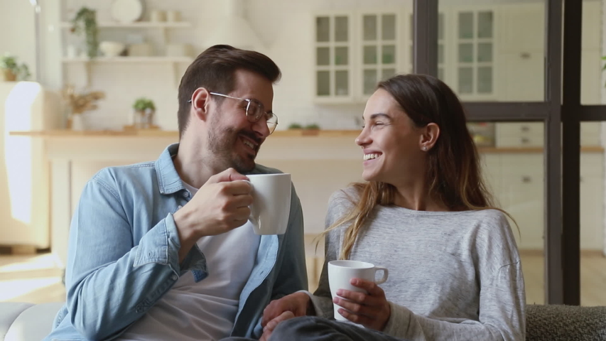 Happy young family couple relaxing talking laughing holding cups drinking coffee tea sitting on sofa together in living room, loving husband and wife bonding enjoying pleasant conversation at home #1032517142