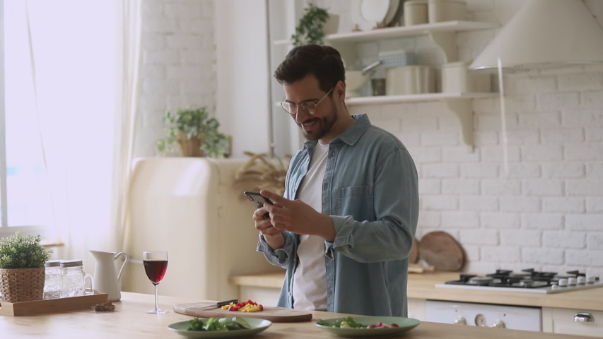 Happy young man preparing romantic surprise using smartphone mobile apps, smiling husband cooking healthy food cutting salad for family dinner in kitchen holding phone search vegan recipe at home