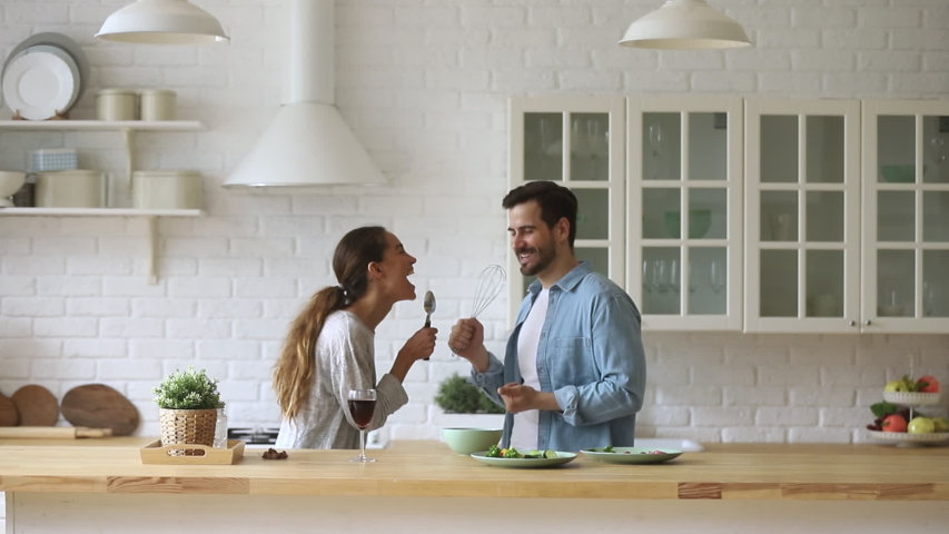 Funny young couple laughing holding kitchenware singing song together dancing to music enjoying cooking in modern cozy kitchen, happy carefree husband and wife having fun preparing food at home Royalty-Free Stock Footage #1032517202
