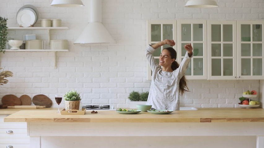 Carefree happy young woman housewife dancing alone cooking meal in modern kitchen, funny cheerful active pretty girl preparing food healthy dinner vegetable salad at home having fun listening music #1032517217
