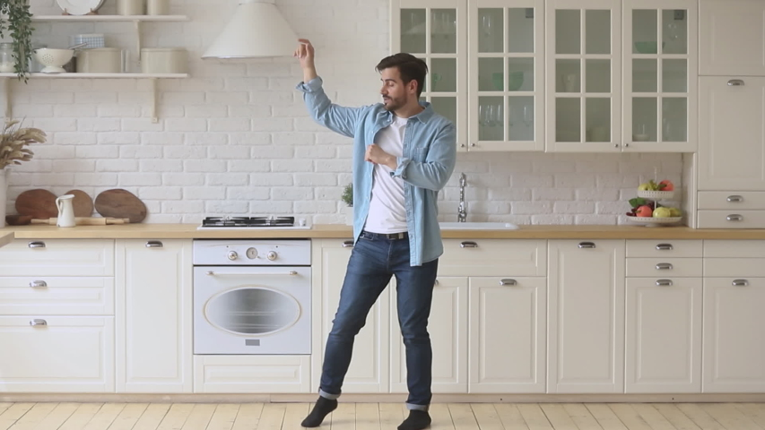 Active carefree young man enjoying funny dance standing in modern kitchen room, happy funky independent guy dancing having fun alone at home listening to pop music moving celebrating freedom #1032517220