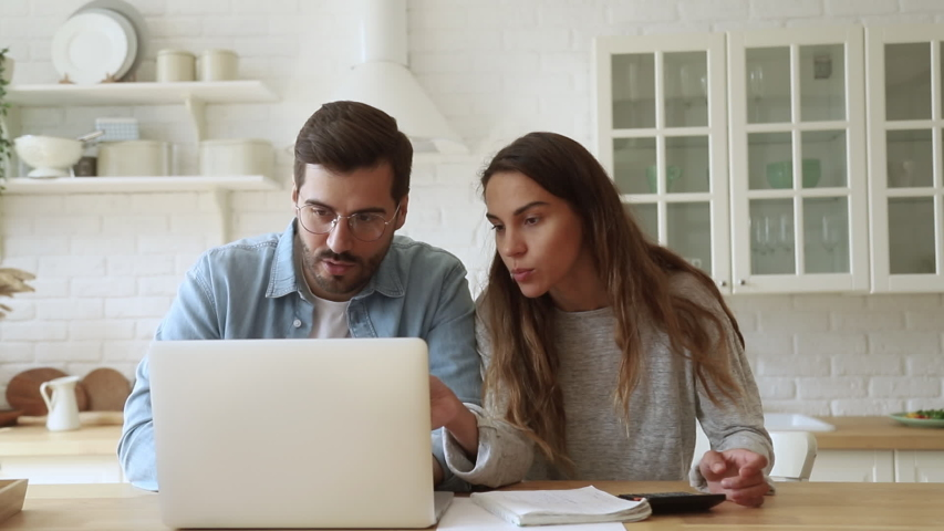 Serious young couple husband and wife pay bills online on website app doing paperwork planning budget discuss finances calculate mortgage payments using laptop computer sit at kitchen table at home