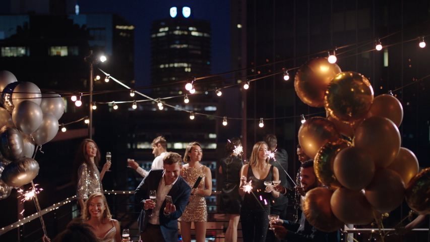 Friends celebrating new years eve party dancing throwing confetti enjoying glamorous celebration wearing stylish fashion at formal social gathering on rooftop at night 4k
