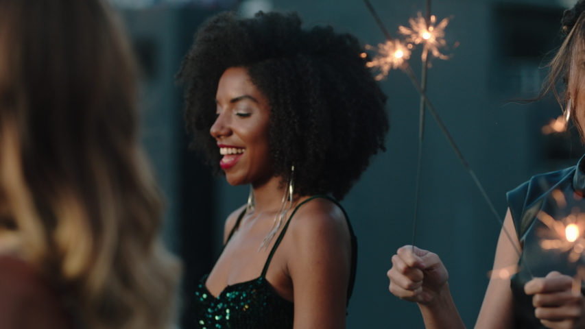New years eve party friends celebrating with sparklers dancing enjoying glamorous evening having fun holiday celebration wearing stylish fashion at social gathering on rooftop at sunset | Shutterstock HD Video #1032520235