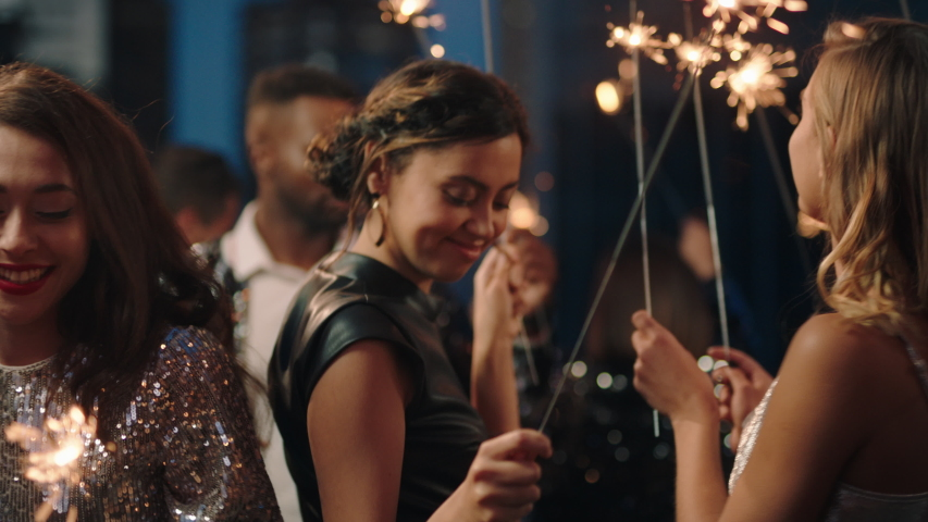 group of friends celebrating with sparklers dancing enjoying glamorous new years eve party having fun holiday celebration wearing stylish fashion at social gathering on rooftop at night Royalty-Free Stock Footage #1032521252