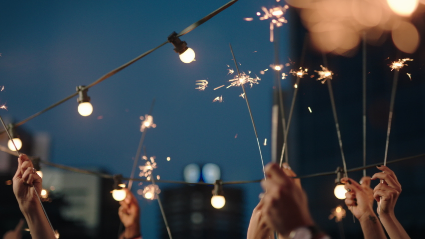 close up hands holding sparklers group of friends celebrating waving sparkler fireworks dancing enjoying new years eve party having fun holiday celebration at evening social gathering on rooftop 4k Royalty-Free Stock Footage #1032521255