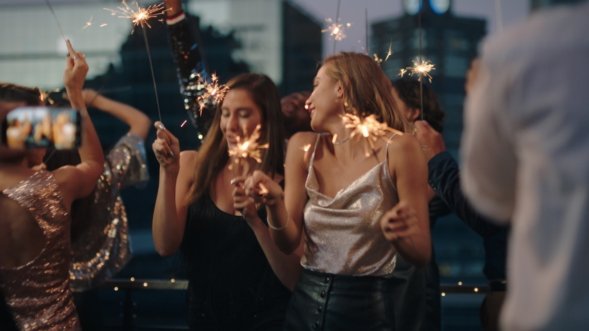 Beautiful young women dancing with sparklers girl friends celebrating new years eve at glamorous party wearing stylish fashion friend using smartphone sharing video of celebration on social media