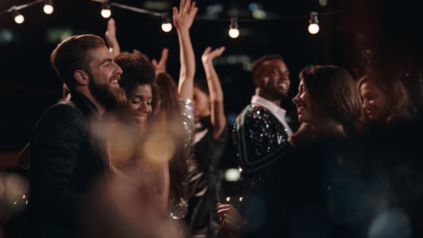 Fun party friends celebrating new years eve dancing throwing confetti enjoying glamorous celebration wearing stylish fashion social gathering on rooftop at night 4k   Shutterstock HD Video #1032521273
