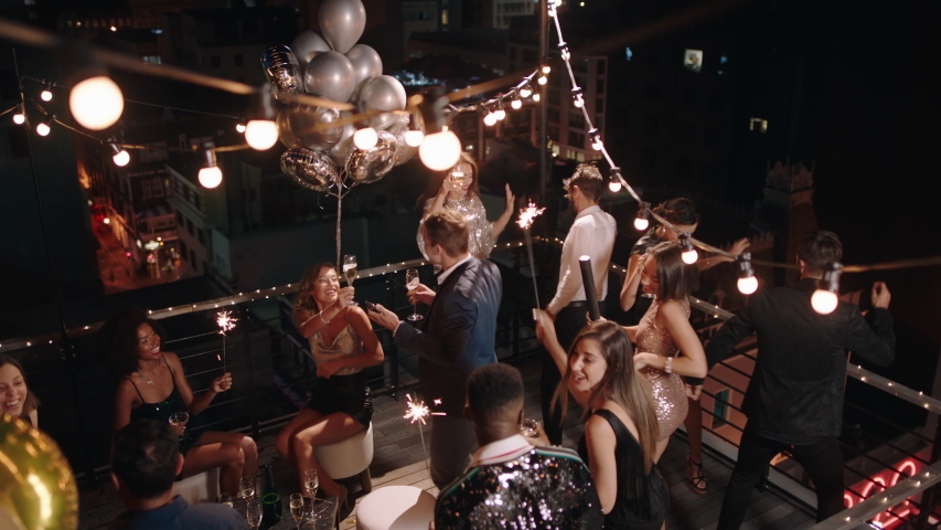 Top view friends celebrating new years eve party dancing throwing confetti enjoying glamorous celebration wearing stylish fashion social gathering on rooftop at night 4k
