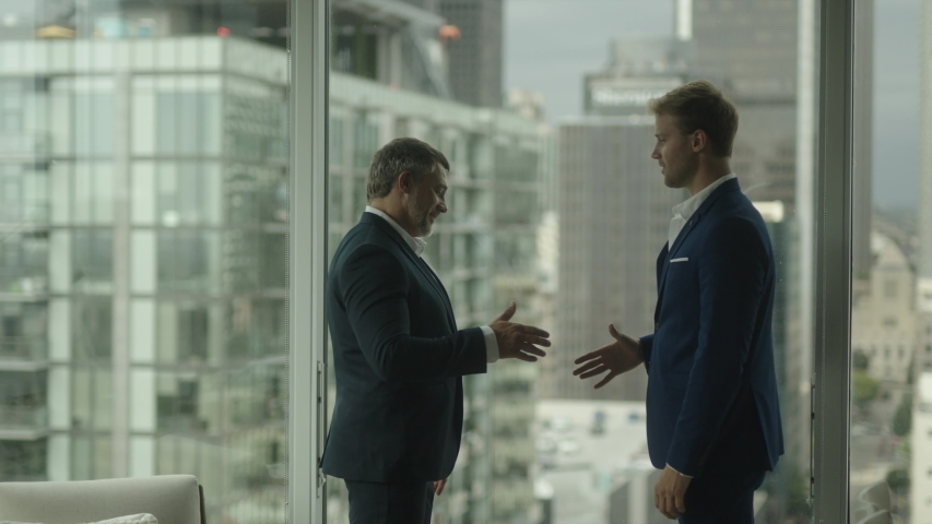 Two business partners do handshake in front of view on downtown and skyscrapers. A good business deal.