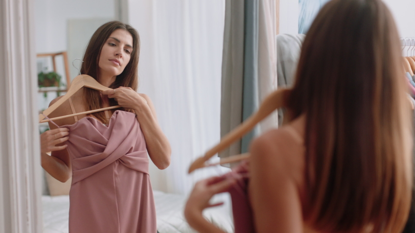 Beautiful young woman getting dressed looking in mirror choosing outfit fashion choice putting on clothes enjoying positive self image feeling confident at home 4k footage