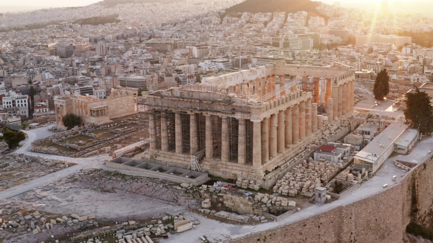 Acropolis city of Athens parthenon, symbol of ancient Greece, aerial view slide from drone on panorama of residential buildings at sunrise summer. Lights sun, lens flare. World Heritage sites. History