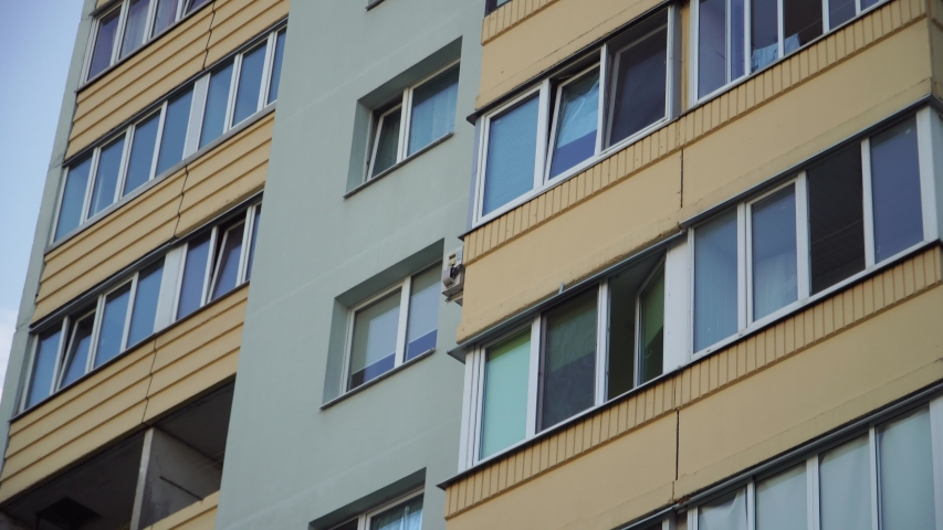 Close up shot of soviet union residential building. Residential building exterior with blue sky background. green house facade. The building features exterior green wall and small balconies