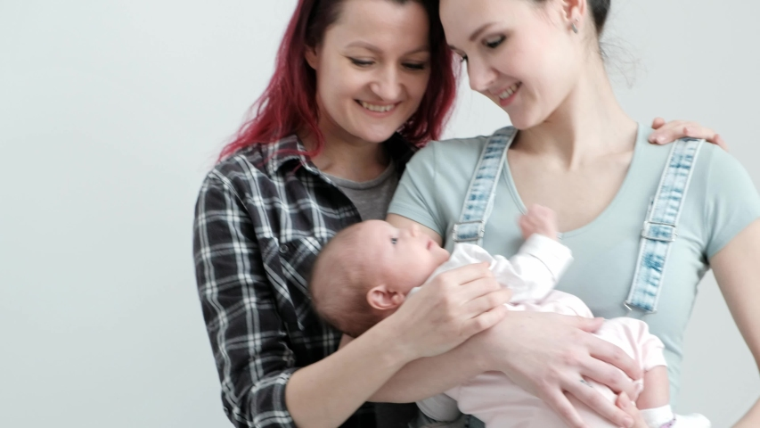 Two young women with dyed red hair and in casual clothes with a baby on a white background. Same-sex marriage and adoption, homosexual lesbian couple. | Shutterstock HD Video #1032537293