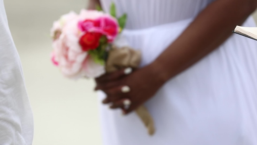 Bride wedding holds a wedding bouquet close-up on the beach. black woman. african american woman.