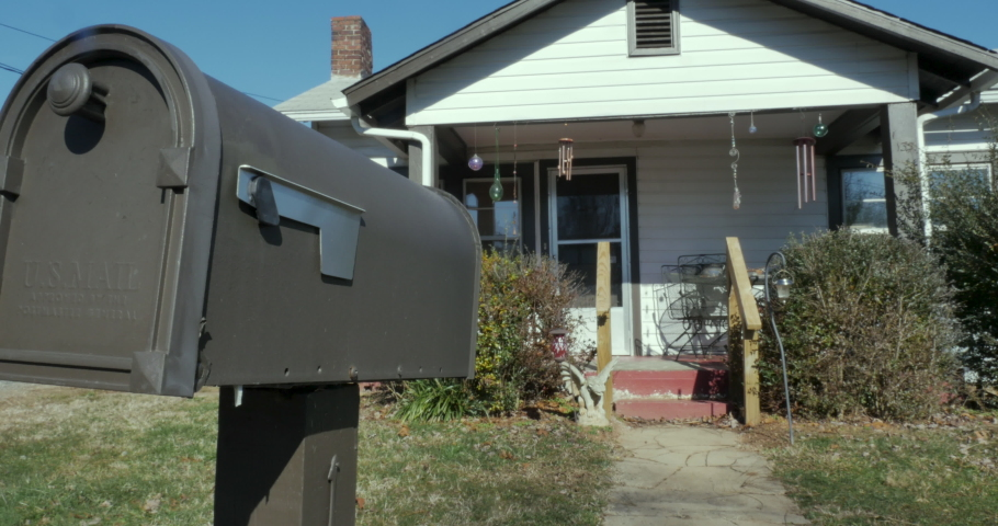 Locked down establishing shot of a small single story home and mailbox during the day   Shutterstock HD Video #1032542804