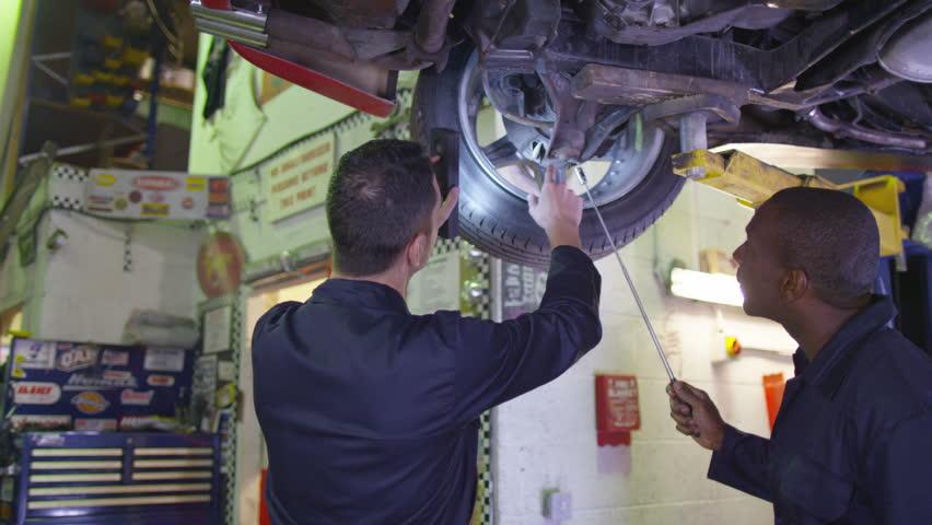 4K Mechanics working underneath a car in garage workshop | Shutterstock HD Video #10325438