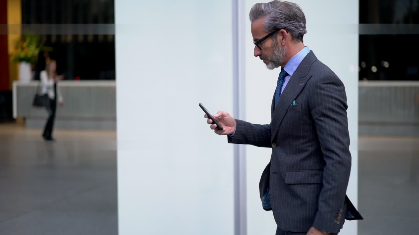 Slow motion effect, Caucasian businessman dressed in formal suit browsing network website using modern smartphone gadget. Middle aged man using mobile phone outdoors in city Royalty-Free Stock Footage #1032547253