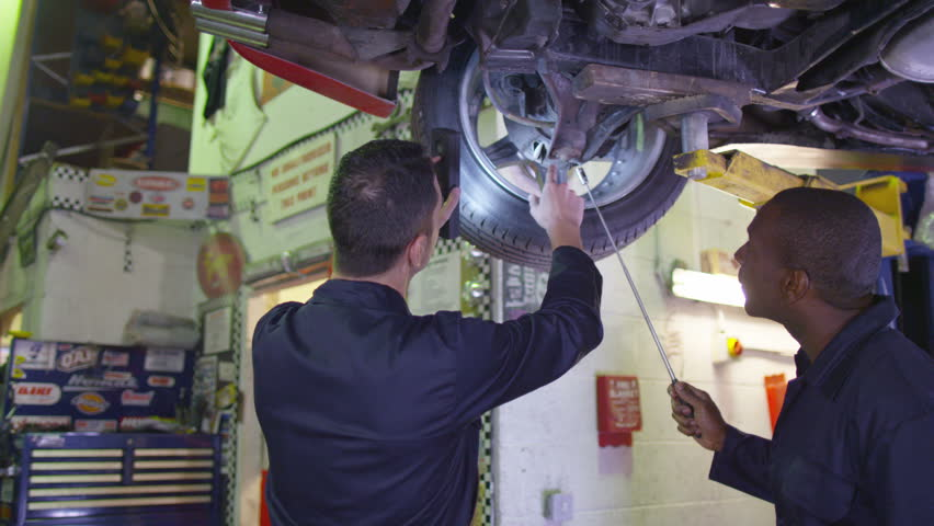 4K Mechanics working underneath a car in garage workshop | Shutterstock HD Video #10325477