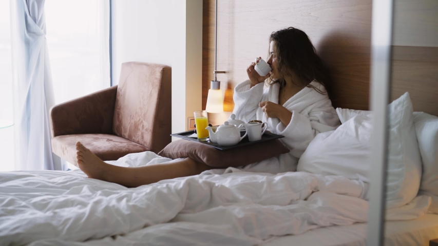 Girl in light hotel apartment with full length windows. Side view woman in white bathrobe lying in bed and have breakfast on small table-tray, enjoying coffee at morning time