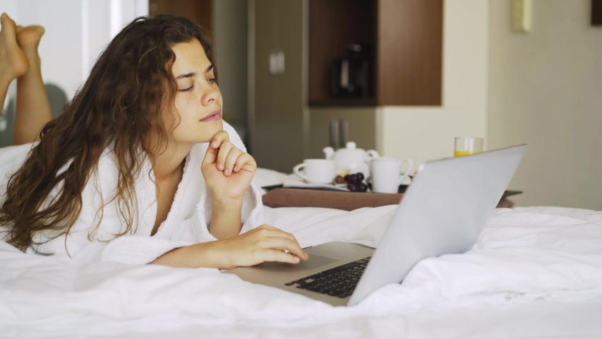 Woman have breakfast in modern hotel apartment. Window light portrait young girl in bathrobe lying on bed using laptop for work. Out of focus tray with meal, juice, plate, teapot on background