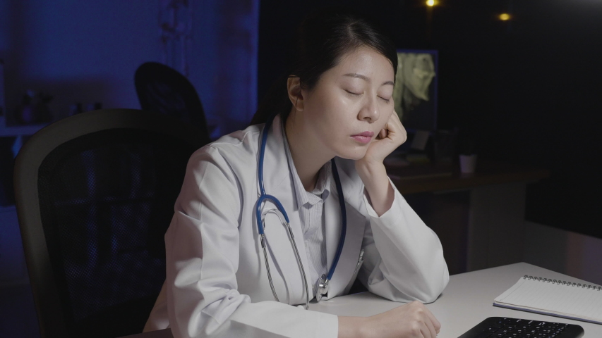 Sleeping doctor woman in clinic office tired of work load at night. female medical worker doze off nod off in dark hospital desk. nurse close eyes head fell on working table at night exhausted