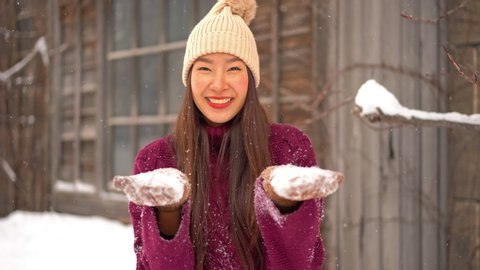 Welcoming winter season, asian lady playing with snow, portrait shot