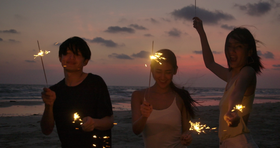 Group of Friends having fun during night party at the seaside with bengal sparkler lights in their hands. Young teenagers partying on the beach with fireworks. Slow motion shot.  Royalty-Free Stock Footage #1032588260