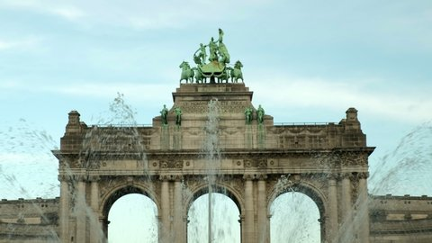 Close shot of top of Triumphal Arch in Brussels through water of fountain