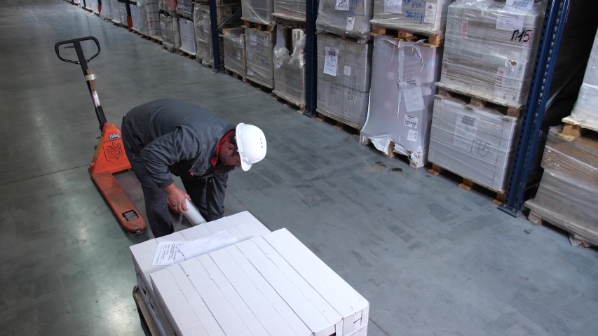 The worker packs a pallet with goods with plastic wrap. | Shutterstock HD Video #1032609311