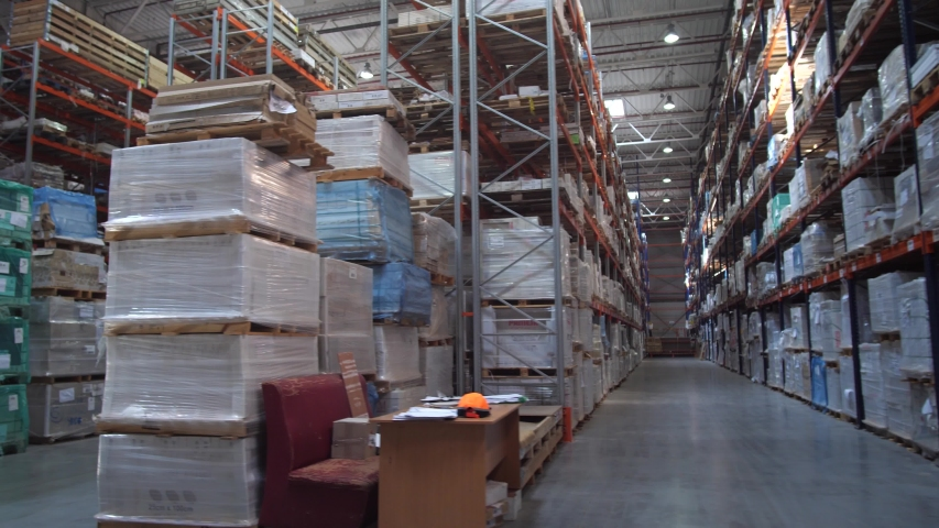 Huge logistic warehouse. Panorama between the rows with shelves. The warehouse is filled with products in boxes. | Shutterstock HD Video #1032609419