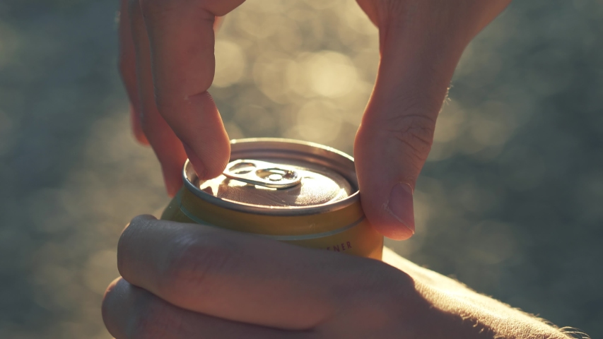 Opening misted wet can of beer sun backlight outdoors