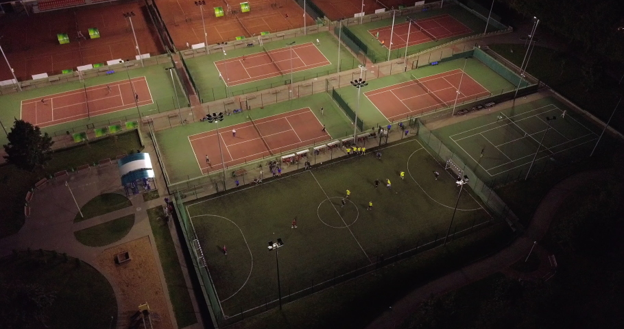 Cinematic aerial drone footage over the university sport field and sports facilities at dusk. Team play football at evening. Tennis courts for recreation and training lit up at night. Sports Complex. Royalty-Free Stock Footage #1032630974
